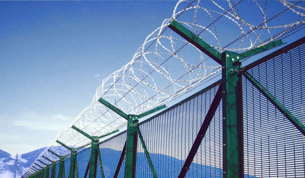 Green 358 mesh panels and concertina wire coils for petrochemical facilities perimeter barrier.