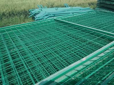Green PVC coated welded wire mesh panels are overlapped on the earth waiting for installation.