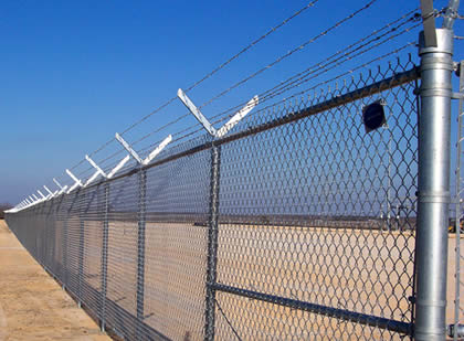Six barbed wires mounted on chain link fence