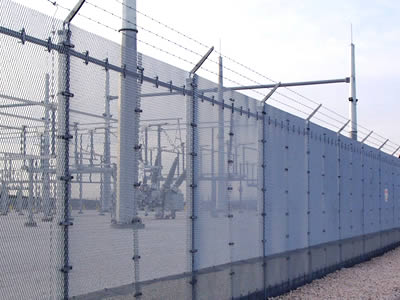 Expanded metal fencing with three lines of barbed wires on topping for power plant security perimeter barrier.