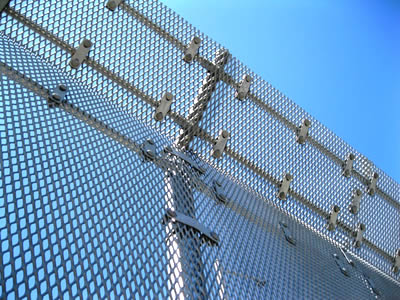 A galvanized expanded metal security fence with posts and three horizontal rails in the blue sky.