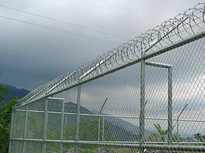 High chain link fence with three rails and razor wires on topping for port perimeter security protection.